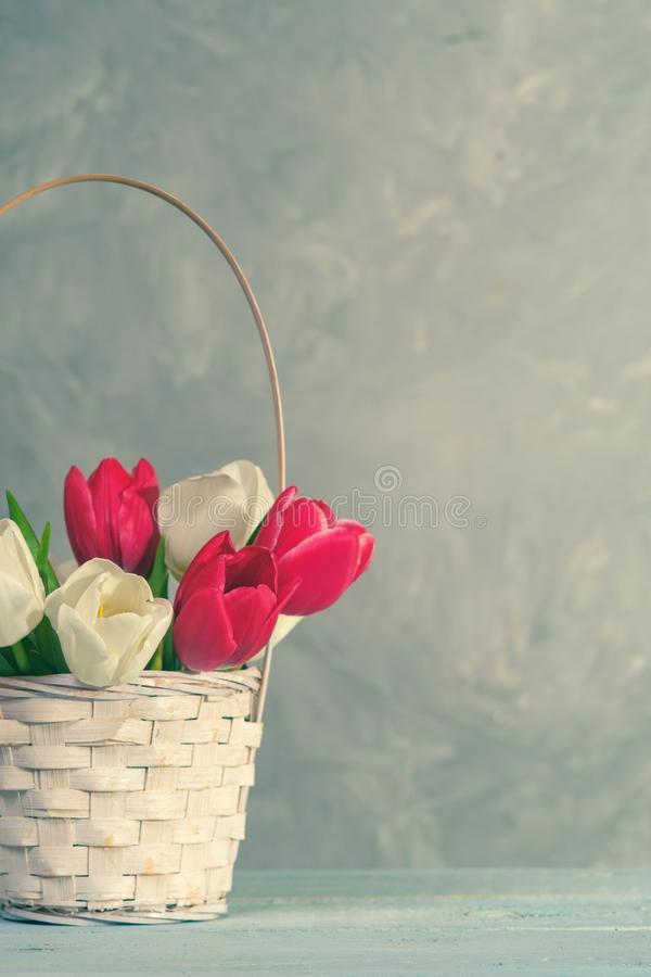 Spring bouquet of tulips in basket on vintage wooden plank. Womans or Mother day royalty free stock photos