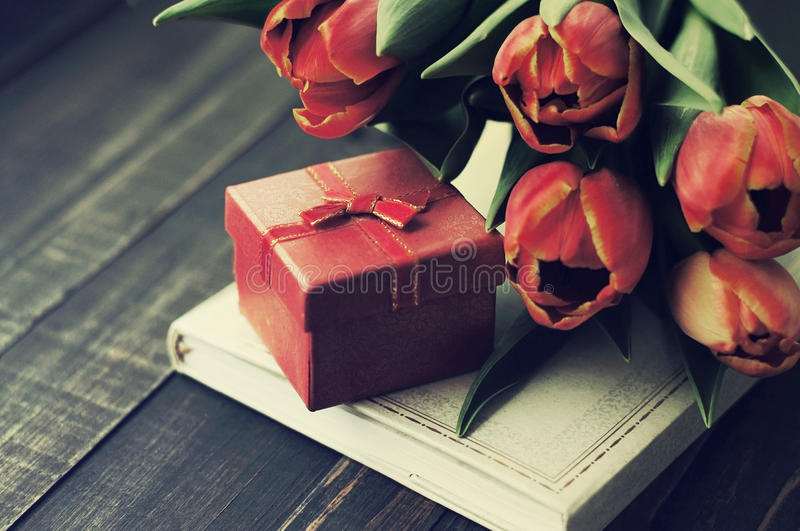 Spring bouquet from tulips and gift packing for your holiday. Red tulips, book and gift red box on a wooden surface. Spring bouquet from tulips and gift packing stock photo