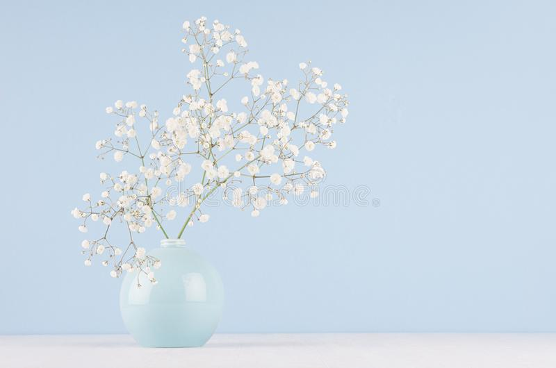 Spring bouquet of white small fluffy flowers in blue smooth circle ceramic vase on soft white wood table and pastel blue wall. royalty free stock photos