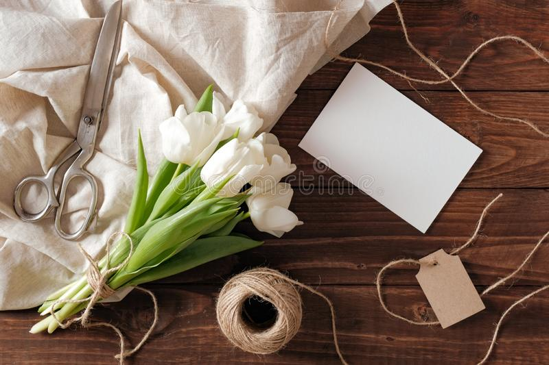 Spring bouquet of white tulip flowers, blank paper card, scissors, twine on rustic wooden desk. Womens day composition on flat lay. Style, above view royalty free stock images