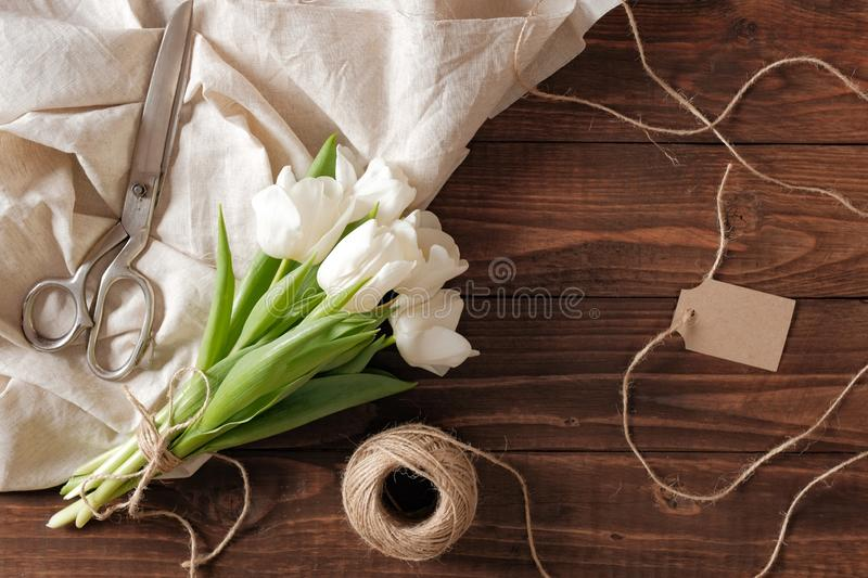 Spring bouquet of white tulip flowers, blank paper card, scissors, twine on rustic wooden desk. Womens day composition on flat lay. Style, above view royalty free stock photography