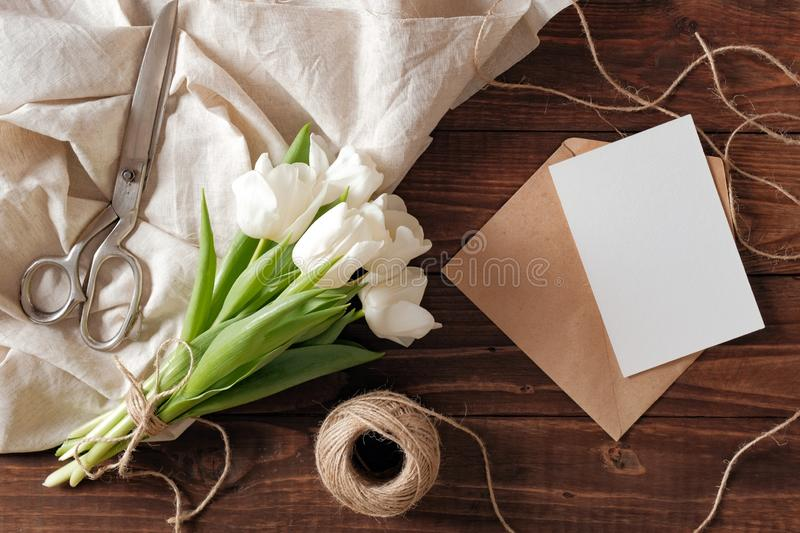 Spring bouquet of white tulip flowers, kraft envelope with blank card, scissors, twine on rustic wooden table. Wedding day composi. Tion on flat lay style, above stock images
