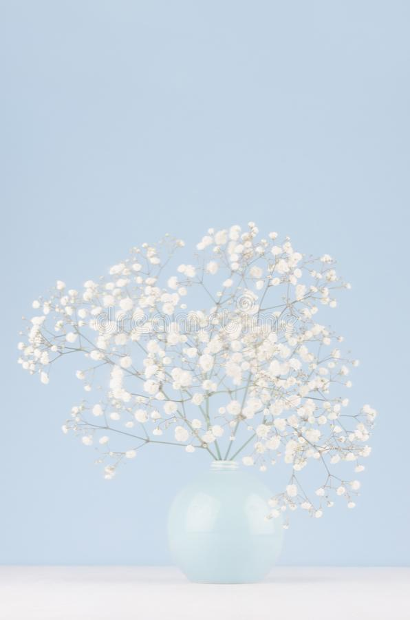 Spring branch with small white flowers in blue sphere vase in soft light blue modern interior, on a white table. stock photos