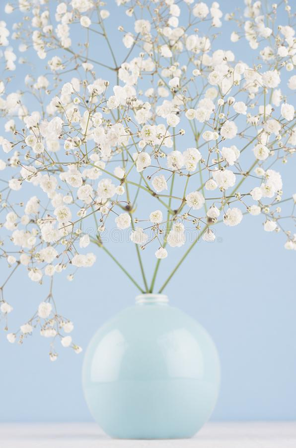 Spring branch with small white flowers in blue sphere vase on soft light blue modern wall and white table, closeup. royalty free stock image