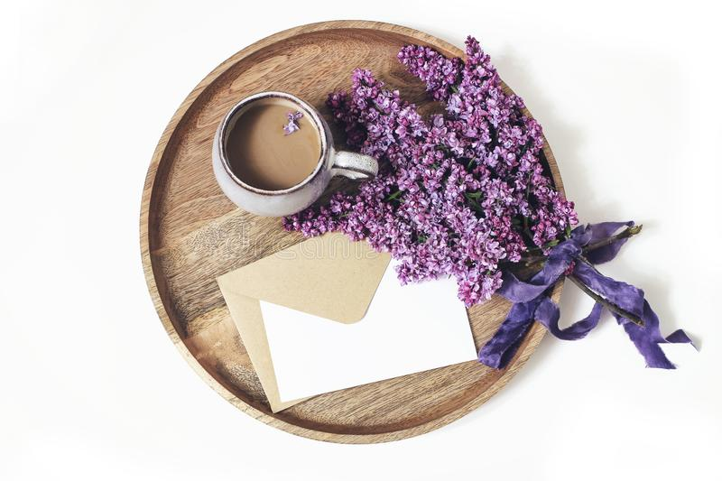 Spring breakfast scene. Blooming purple lilac branches, silk ribbon, cup of coffee and wooden tray isolated on white stock images