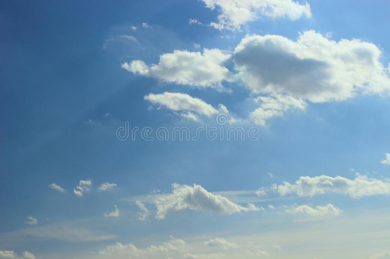 Spring bright blue sky with small clouds in the sun rays. the concept of ecology of life royalty free stock photo