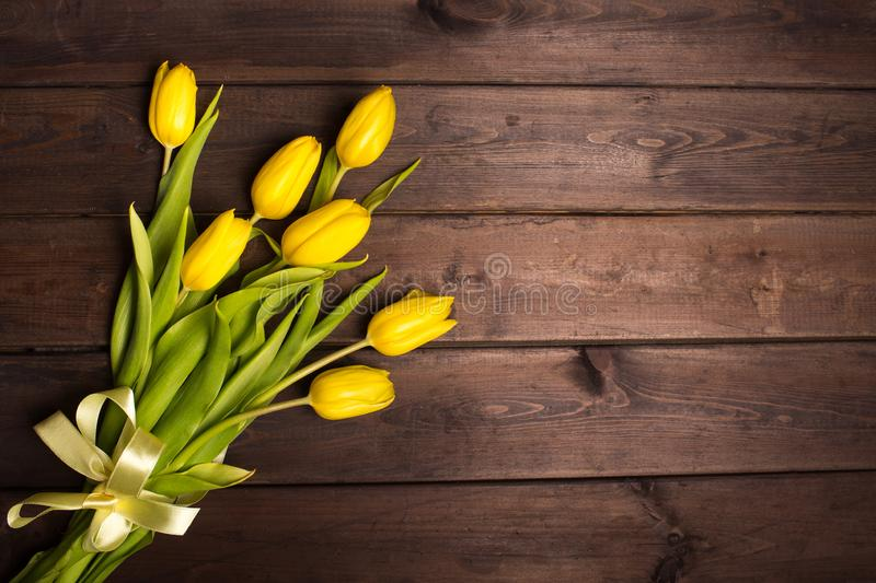 Spring card: yellow tulips on a dark wooden background. Top view, lay flat stock photos