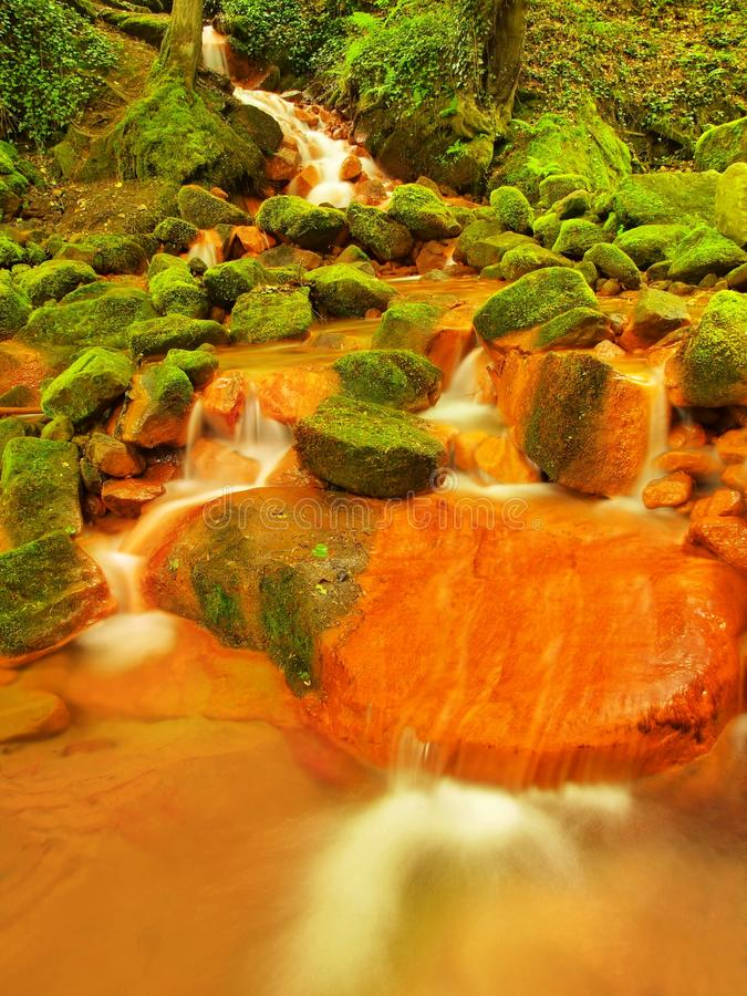 Spring cascades in rapid stream of mineral water. Red ferric sediments on big boulders stock photo