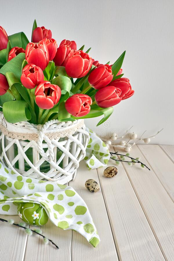 Spring celebration background: bunch of red tulips, spring decorations and quail eggs on light wood royalty free stock images
