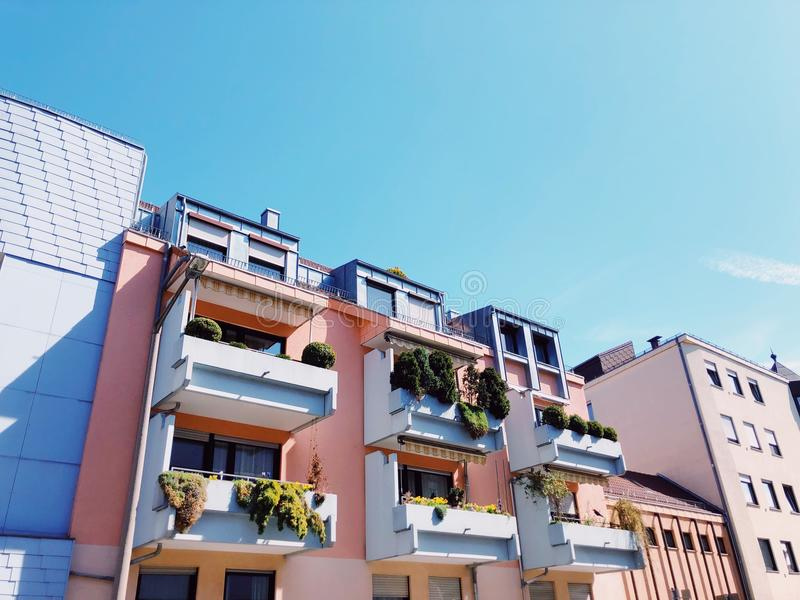 Spring in the city. Colored houses with pots of green on balcony stock image