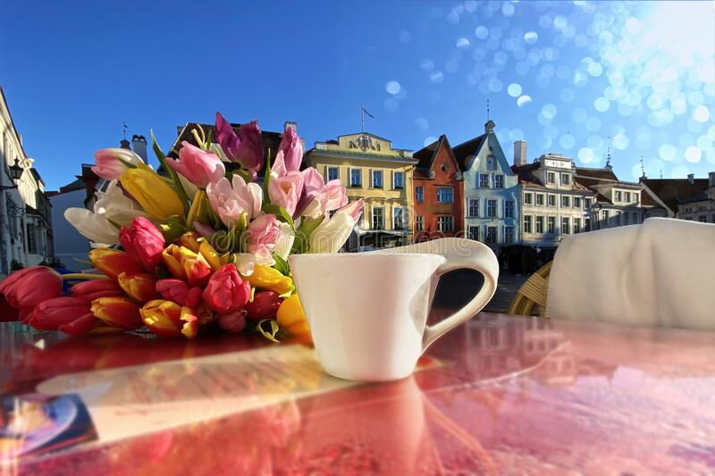 Spring city ,street cafe in Tallinn town square ,cup of coffee with heart on table top and flowers tulip ,blue sky,sunny spring da stock photography