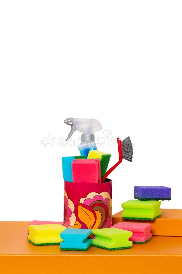 Spring cleaning background. Close-up of house cleaning products and cleaning supplies on orange wooden table isolated on a white. Background. Household chore royalty free stock images