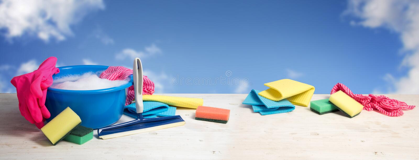 Spring cleaning banner, blue plastic bowl with soap foam, pink r. Ubber gloves, rags, sponges and window wiper on white wooden planks against a blue sky with stock images