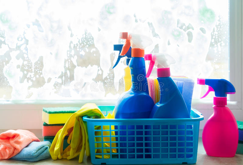 Spring cleaning concept. Spring cleaning - container with sprays, gloves and rubbers on windowsill stock photography