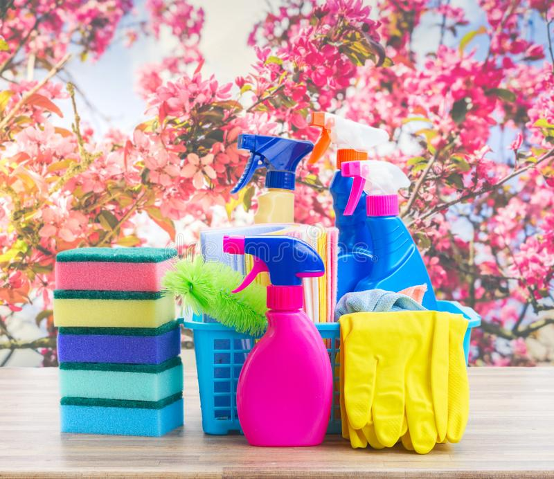 Spring cleaning concept. Colorful sprays bottles and rubbers on wooden table over spring background royalty free stock photos