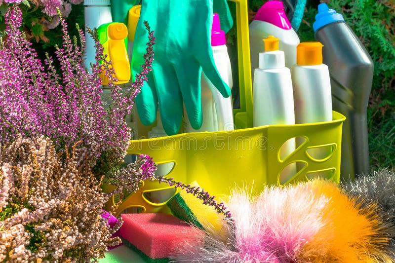 Spring cleaning concept with supplies, colorful sprays, bottles and rubbers with flower stock image