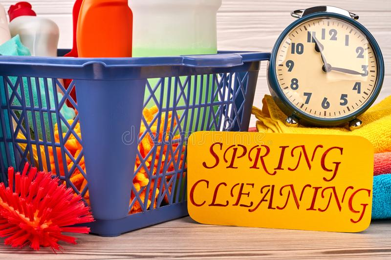 Spring cleaning concept with supplies. Close up cleaning products, alarm clock and paper card. Speed clean for your house. Make cleaning of your home easier royalty free stock photos