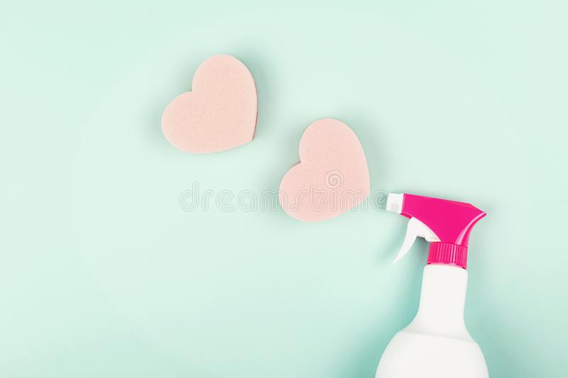 Spring cleaning spray on light green background. Spring cleaning concept. Spray and heart shape sponges on light green background. Trendy toning. Flat lay, top stock photos