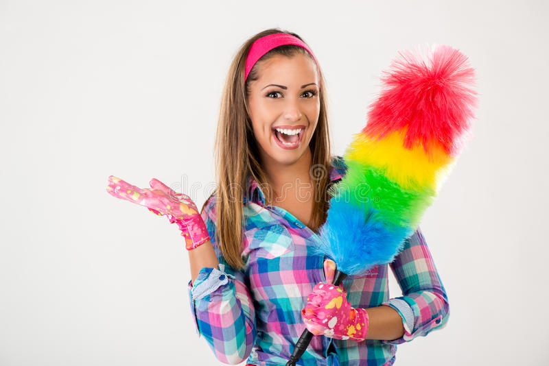 Spring Cleaning Woman. Portrait of a smiling young beautiful spring cleaning woman. She is holding a duster and looking at camera stock photos