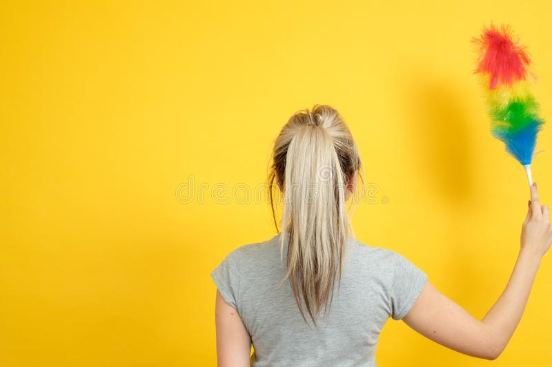 Spring cleanup woman feather duster copy space. Early spring regular cleanup. Woman with feather duster backview. Copy space on yellow background stock photography