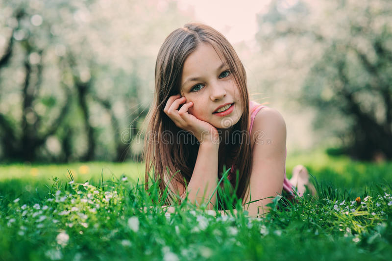 Spring closeup outdoor portrait of adorable 11 years old preteen kid girl. Spending spring holidays in beautiful blooming cherry garden royalty free stock image