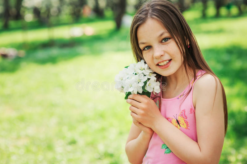 Spring closeup outdoor portrait of adorable 11 years old preteen kid girl. Spending spring holidays in beautiful blooming garden royalty free stock photo