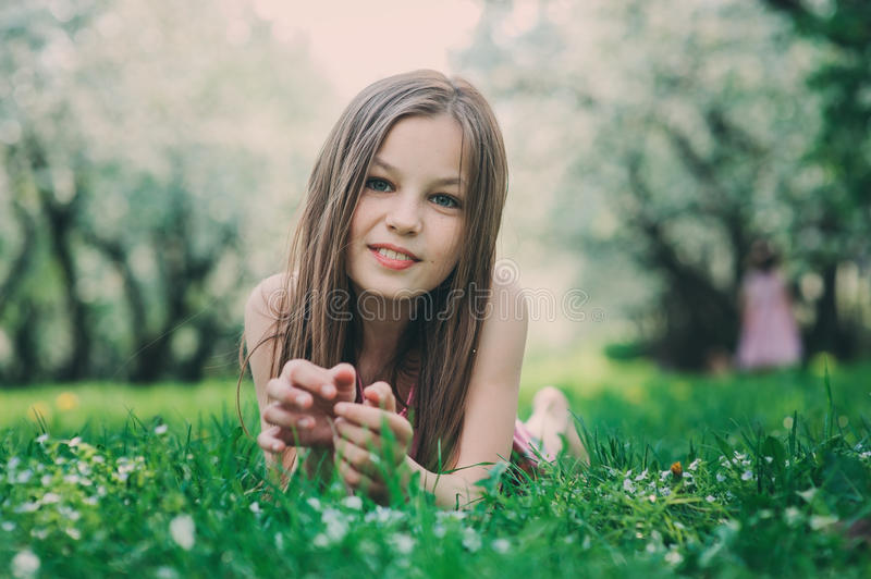 Spring closeup outdoor portrait of adorable 11 years old preteen kid girl. Spending spring holidays in beautiful blooming garden royalty free stock image