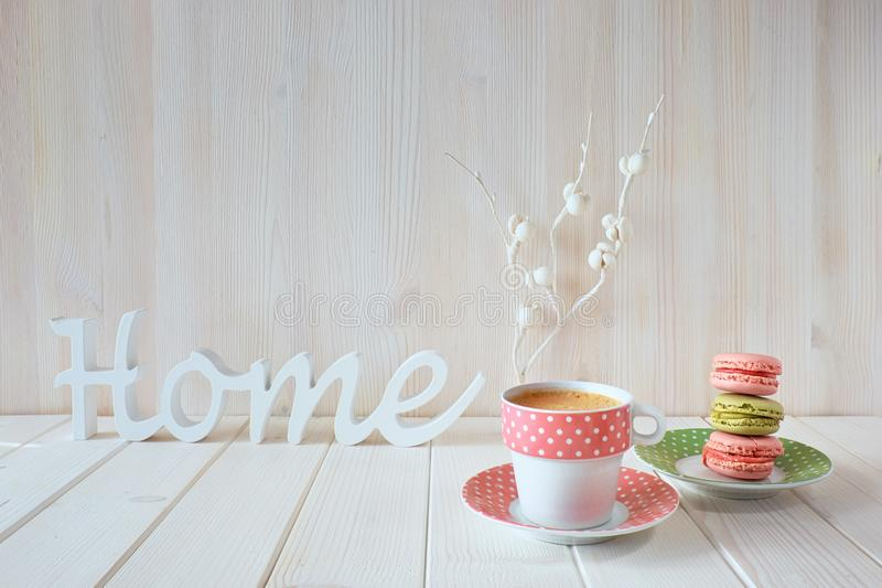 Spring coffee background. The word. `Home` made of wood, white paper flowers, espresso and macarons stock photo
