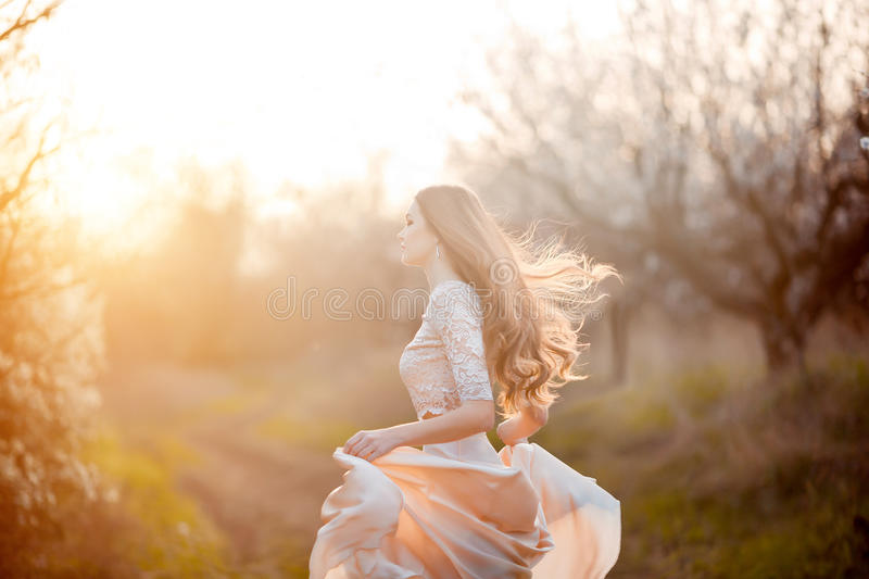 Spring is coming. Happy beautiful young woman running and having fun in blossom park. stock photos