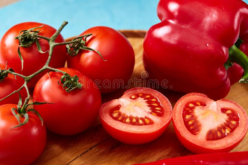Composition of tomato bunch and halves and sweet pepper on wooden plate, top view, close-up, selective focus. stock images