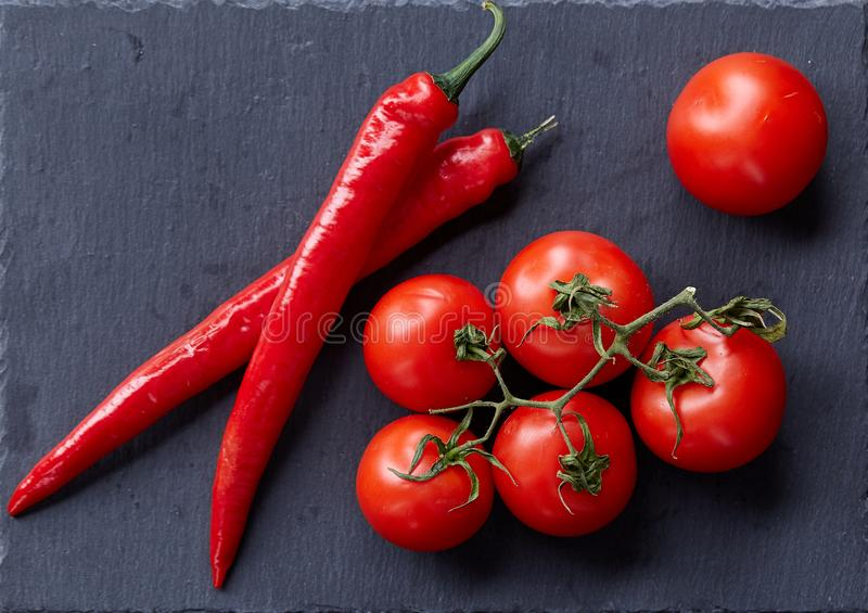Composition of tomato bunch and hot pepper on black piece of board, top view, close-up. stock image