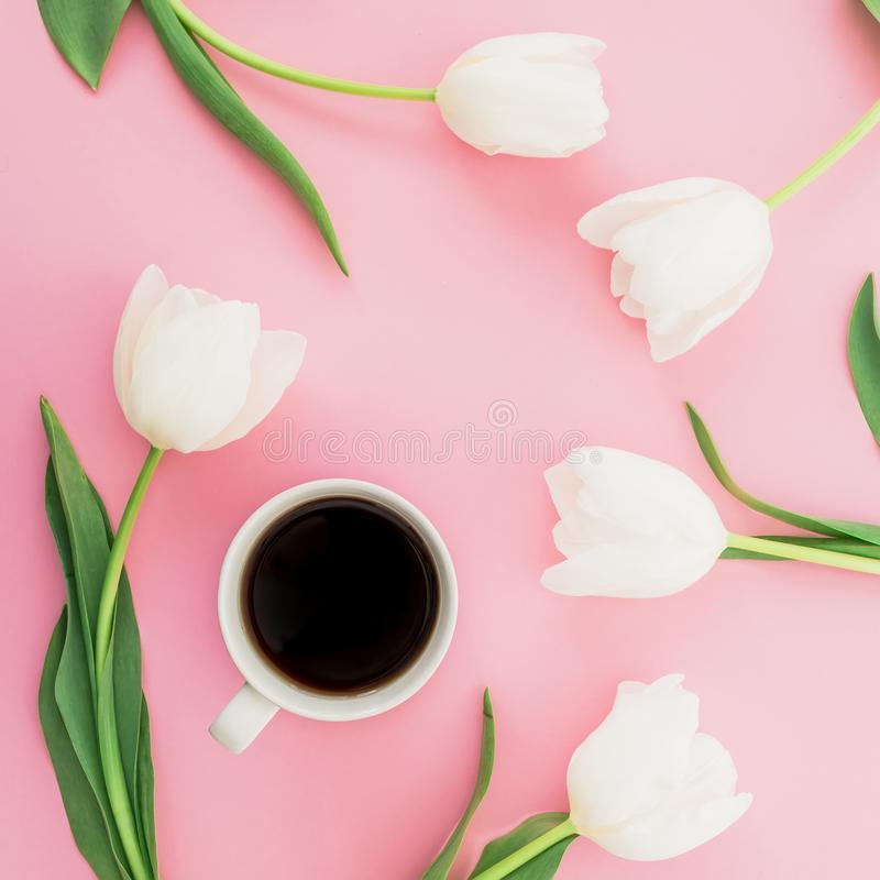 Spring composition with tulip flowers and mug of coffee on pink background. Flat lay, top view. stock image