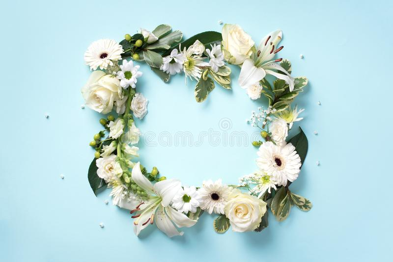 Spring composition of white flowers on blue paper background with copy space. Creative layout. Flat lay. Top view stock photos