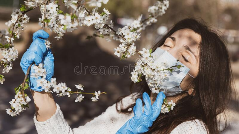 Spring and the coronavirus epidemic. Lifestyle in the new environment concept. Spring and the coronavirus epidemic. A young woman in medical gloves and a stock photo