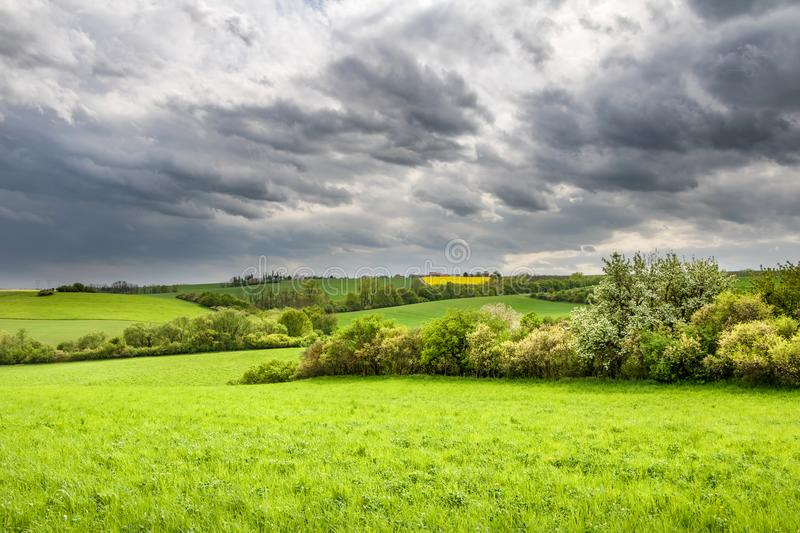 Spring countryside with green meadows and trees under dramatic s. Amazing spring countryside with green meadows and trees under dramatic sky - Czech Republic royalty free stock photos