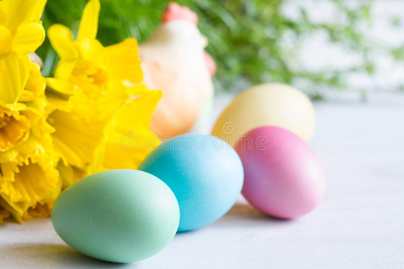Spring daffodils and colorful easter eggs on blurred background. Closeup royalty free stock images