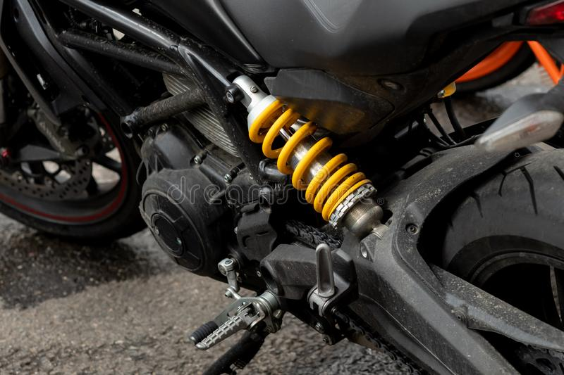 Spring dampers yellow dirty black motorcycle. Shock, machine, bike, detail, engine, equipment, metal, object, part, red, repair, shiny, suspension, absorber stock image