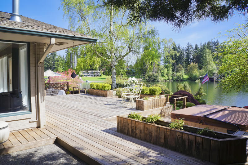 Spring deck and house view with lake and tub. stock image
