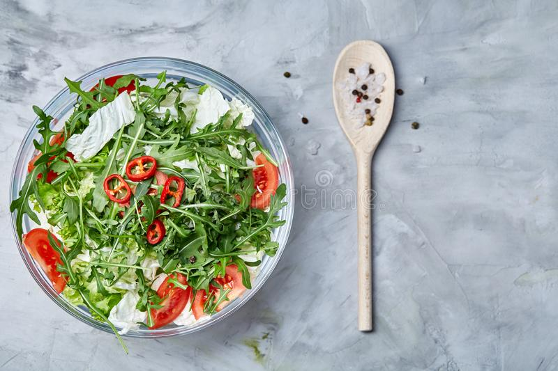 Dietary mixed salad in glass sultana served with wooden spoon on white background, selective focus royalty free stock photo