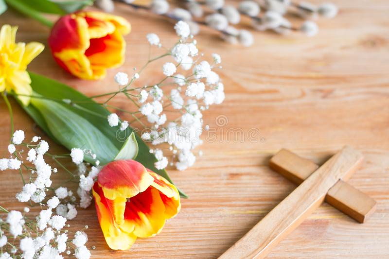 Spring easter flowers and cross on wooden background. Abstract royalty free stock photography