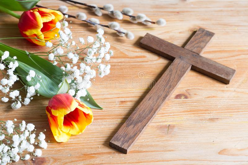 Spring easter flowers and cross on wooden background. Abstract royalty free stock image