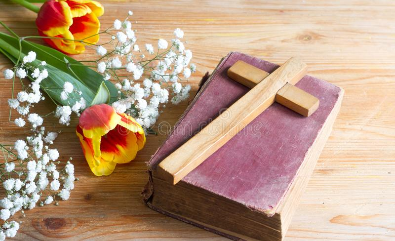 Spring easter flowers and cross on wooden background. Abstract royalty free stock images