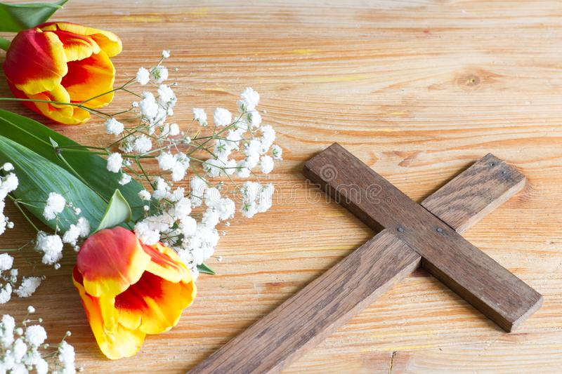 Spring easter flowers and cross on wooden background royalty free stock image