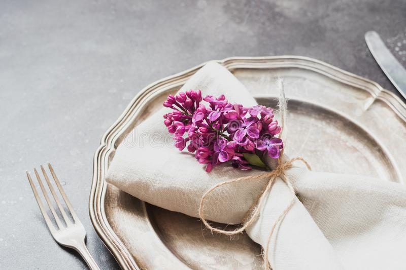 Spring elegant table place setting with violet lilac, silverware on vintage table. Close up. Spring elegant table place setting with violet lilac flowers stock photos