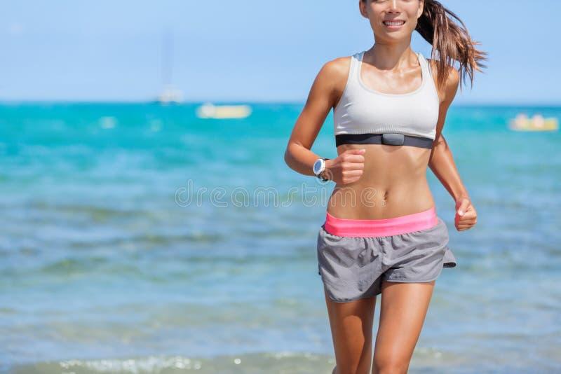 Spring för kvinna för löpare för bildskärm för hjärtahastighet på stranden arkivbild