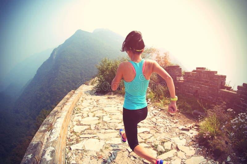 Spring för kvinnalöpareidrottsman nen på slinga på den kinesiska stora väggen arkivbild