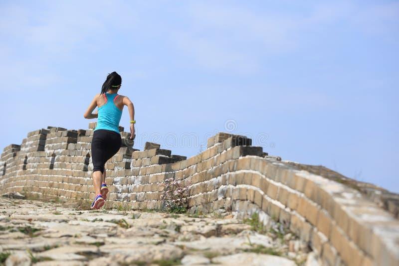 Spring för kvinnalöpareidrottsman nen på slinga på den kinesiska stora väggen royaltyfria foton