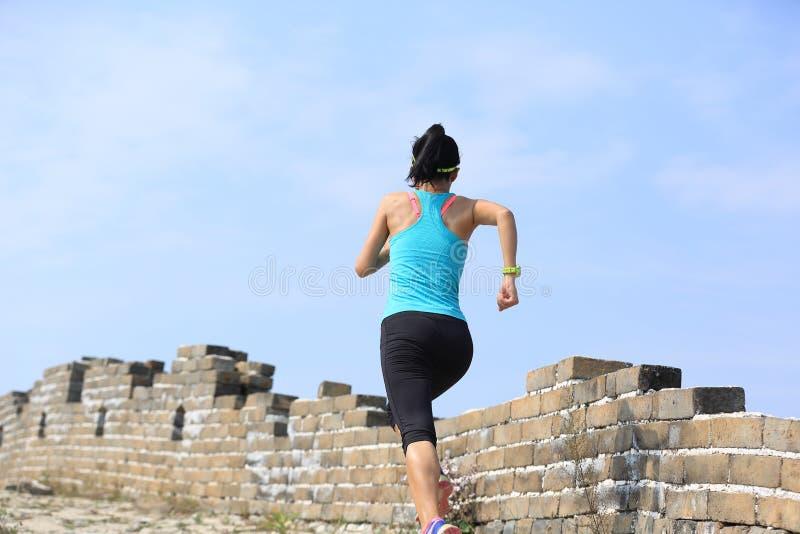 Spring för kvinnalöpareidrottsman nen på slinga på den kinesiska stora väggen royaltyfri bild