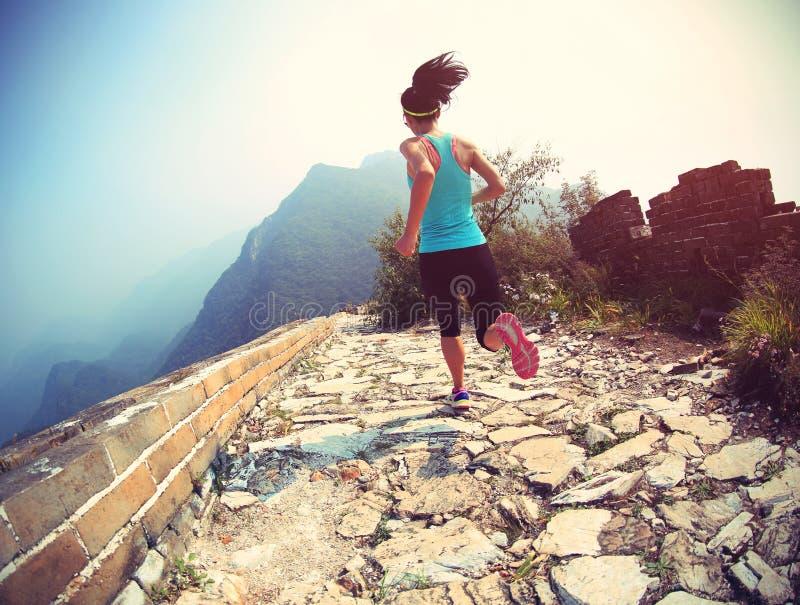 Spring för kvinnalöpareidrottsman nen på slinga på den kinesiska stora väggen fotografering för bildbyråer