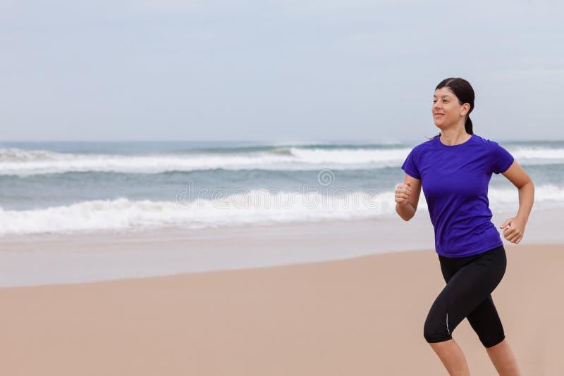 Spring för kvinnlig idrottsman nen på stranden arkivbilder